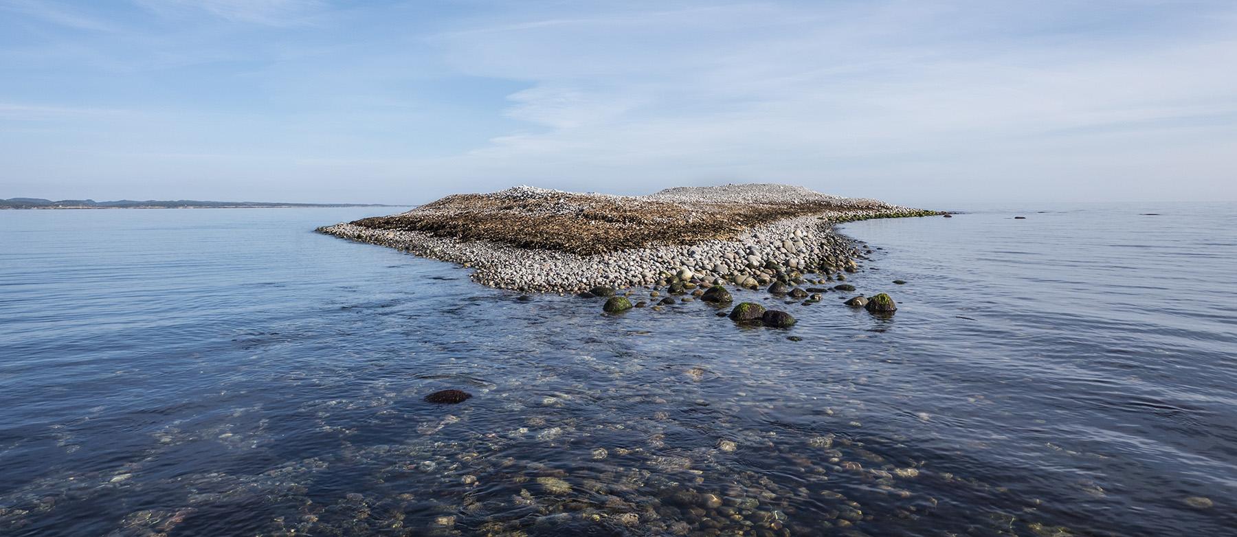 Endemorenen fra siste istid – raet – dukker opp av havet som en haug rullestein og danner øya Målen i Raet nasjonalpark. Foto: Øystein Paulsen