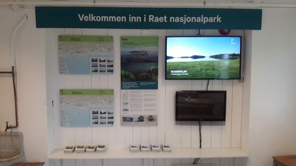 Informasjonsveggen i kafeteriaen i Norsk Hagebruksmuseum på Dømmesmoen gir informasjon om hvor og hva Raet nasjonalpark er – og hvor den kan oppleves i Grimstad kommune.